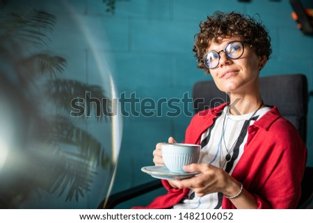 Serene female with curly hair having tea or coffee while relaxing in cafe Stock photo © pressmaster