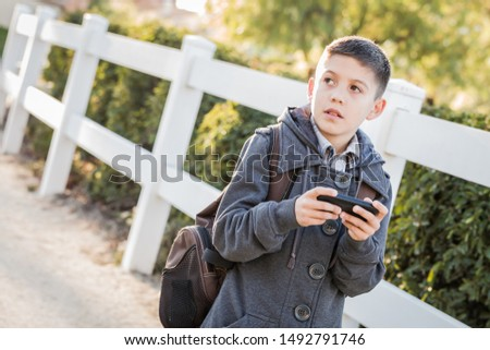 Concerned Young Hispanic Boy Walking With Backpack Holding Cell  Stock photo © feverpitch