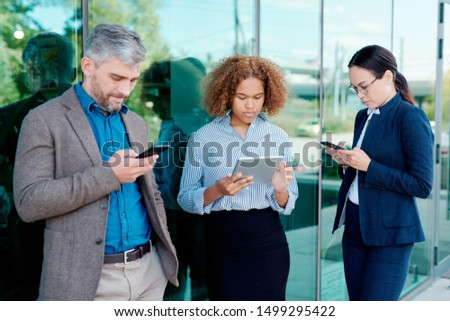 Group of millennials in formalwear using touchpad and smartphones outdoors Stock photo © pressmaster
