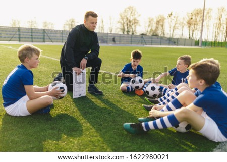 Boys Training Football on Pitch Witch Youth Coach. Group of Young School Age Boys Stock photo © matimix