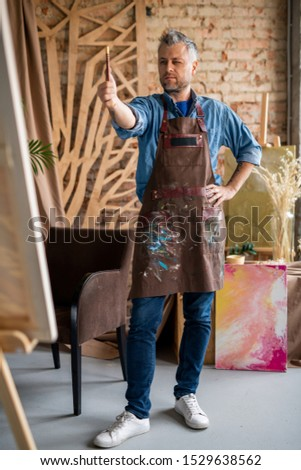 Artist with paintbrush determining center of painting or paper sheet Stock photo © pressmaster