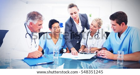 Stock photo: Front view of happy young female doctor discussing medical report with senior man on clipboard in ga