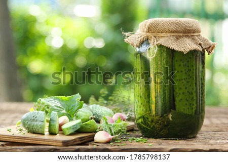 Glass jar of pickled cucumbers with herbs on rustic wooden background. Marinated and canned food. To Stock photo © Virgin