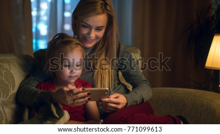cute girl and her mother with smartphone watching video or making selfie stock photo © pressmaster