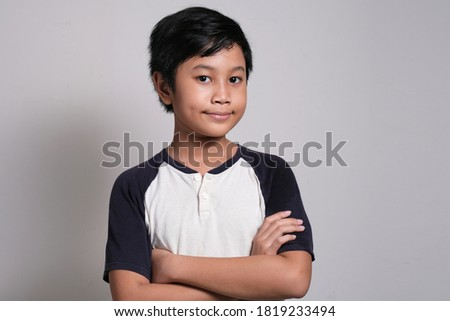 Front of an Asian schoolboy with arms crossed standing against greenboard in a classroom at elementa Stock photo © wavebreak_media