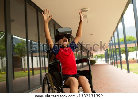 Front view of happy mixed-race disabled schoolboy using virtual reality headset in corridor at eleme Stock photo © wavebreak_media