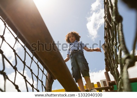 Low angle view of a mixed-race schoolgirl walking on net bridge in the school playground on a sunny  Stock photo © wavebreak_media