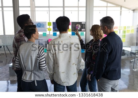 Rear view of standing mixed race businuess colleagues interacting with each other in modern office.  Stock photo © wavebreak_media