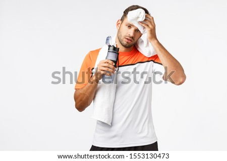 Handsome sportsman wipe sweat from forehead with towel on neck, tilt head and looking tired after go Stock photo © benzoix