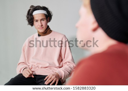 Serious man in powdery pink pullover and white headband interacting with vlogger Stock photo © pressmaster