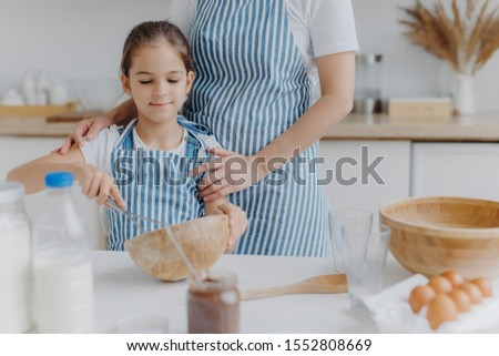 Cropped image of affectionate mother in apron embraces daughter who learns how to make pasty, holds  Stock photo © vkstudio
