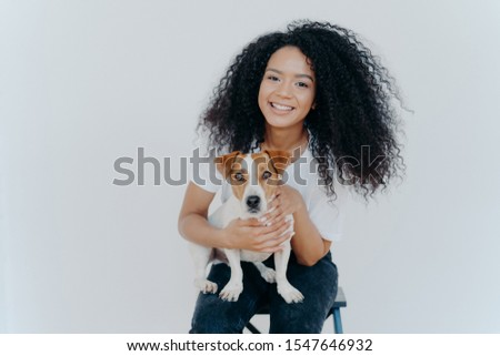 Photo of glad dark skinned female being forever together with pedigree puppy, enjoys leisure at home Stock photo © vkstudio