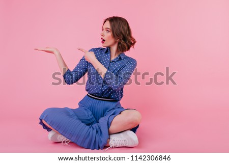 Studio shot of restful beautiful Caucasian woman sits on chair, wears shirt, white trousers and shoe Stock photo © vkstudio