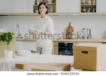 Happy brunette woman in casual outfit, moves into new house, unpackes boxes with kitchen dishes, hol Stock photo © vkstudio