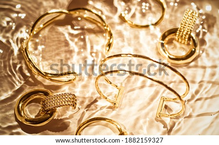 Golden bracelets, earrings, rings, jewelery on gold water backgr Stock photo © Anneleven