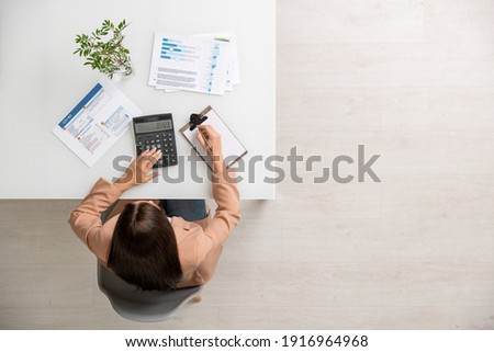 Overview of hands of young businesswoman with pen making notes in notebook Stock photo © pressmaster