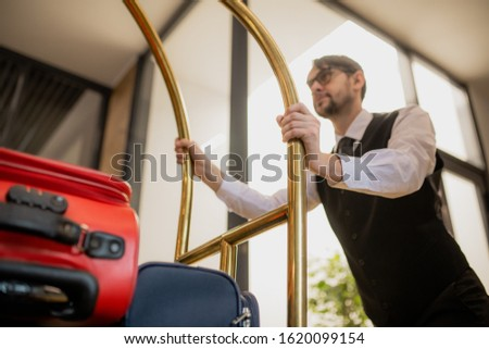 Contemporary porter holding by handles while pushing cart with suitcases Stock photo © pressmaster