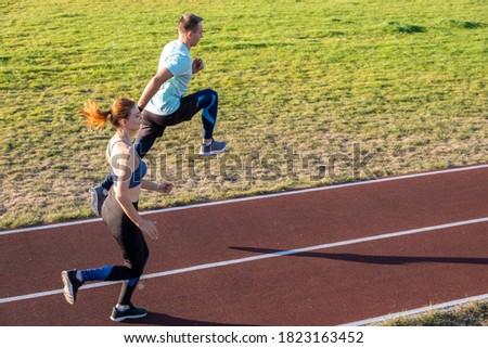 Imagem enérgico mulher homem exercício estádio Foto stock © deandrobot