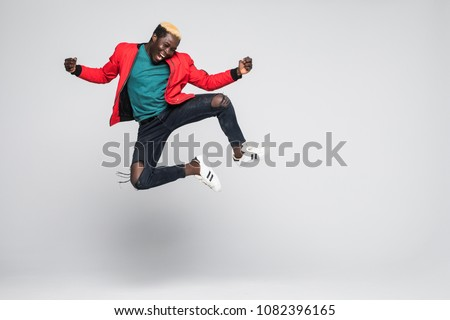 Full length image of happy african american guy smiling and danc Stock photo © deandrobot