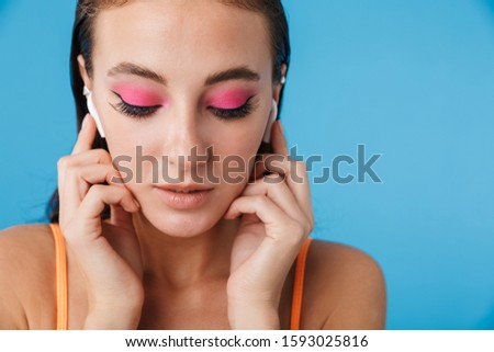 Photo closeup of brunette focused woman posing and using earpods Stock photo © deandrobot