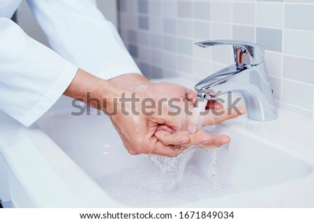 doctor disinfecting his hands with hand sanitizer Stock photo © nito