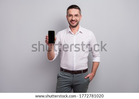 Cheery young businessman showing display of mobile phone. Stock photo © deandrobot
