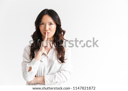 Image of asian girl holding finger on lips and asking to keep si Stock photo © deandrobot