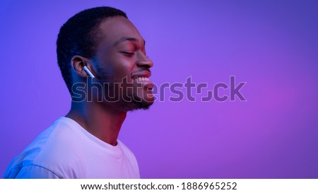 Happy, pleased handsome man enjoy listening favorite music, holding smartphone, press earphone to ea Stock photo © benzoix