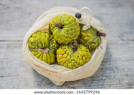Cherimoya in a reusable bag on a stylish wooden kitchen surface. Zero waste concept, plastic free co Stock photo © galitskaya