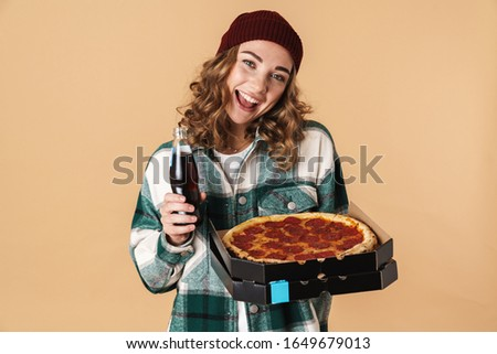 Photo of pretty pleased woman holding box with pizza and drinking soda Stock photo © deandrobot