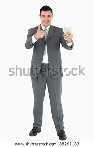 Businessman with banknotes giving thumb up against white background stock photo © wavebreak_media