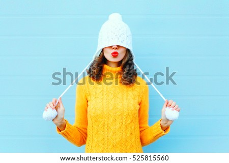 Beautiful young woman in knitted hat and sweater blows on hot te Stock photo © Nobilior