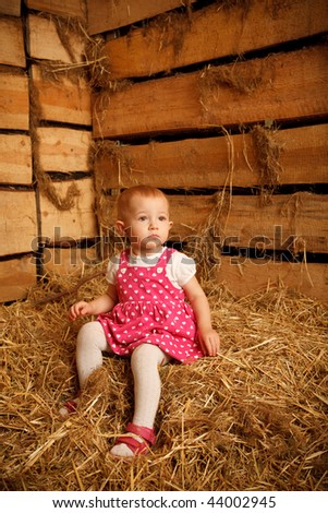 Little girl is sitting on pile of straw in hayloft against the wall of boards. Vertical format. Stock photo © Paha_L