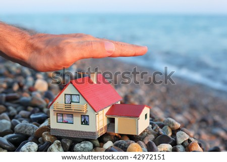 model of house with garage on stony beach in evening, Man's hand Stock photo © Paha_L