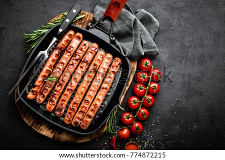 Grilled sausages bratwurst in grill frying-pan on black background. Top view. Traditional German cui Stock photo © yelenayemchuk