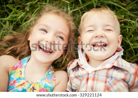 Portrait of little blonde happy smiling caucasian boy in orange t-shirt with hand near his face on g Stock photo © Traimak