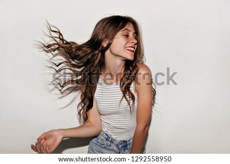 Portrait of brunette positive woman 20s with long hair rejoicing Stock photo © deandrobot
