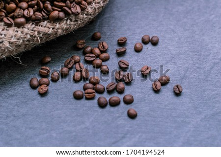 Stock photo: Purse with roasted beans and wooden scoop on black stone concret