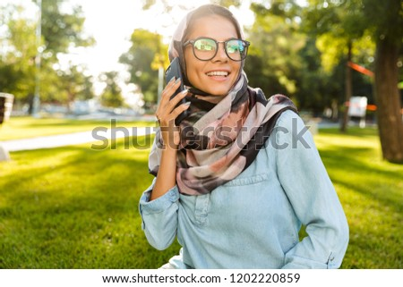 Photo of brunette islamic woman wearing headscarf speaking on mo Stock photo © deandrobot