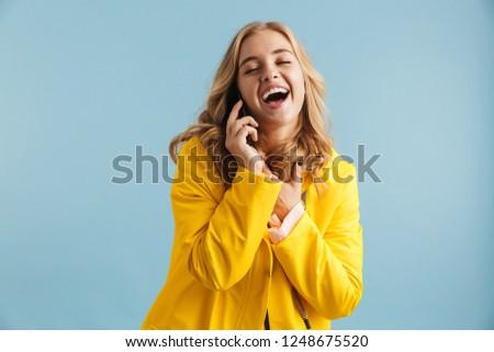 Image of joyful woman 20s wearing yellow raincoat laughing while Stock photo © deandrobot