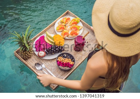 Young woman relaxing and eating fruit plate by the hotel pool. Exotic summer diet. Photo of legs wit Stock photo © galitskaya
