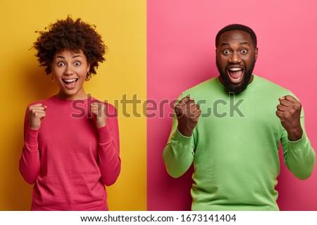photo of joyous african american couple wearing colorful sweatsh stock photo © deandrobot