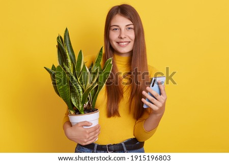 Image of pretty woman gardener standing over plants in conservat Stock photo © deandrobot