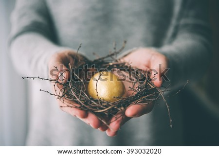 Golden painted small eggs hold the hands of a woman on a gray background. Concept of profit and weal Stock photo © artjazz