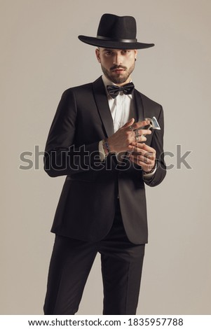 fashion guy adjusting bowtie while standing with hand in pocket Stock photo © feedough