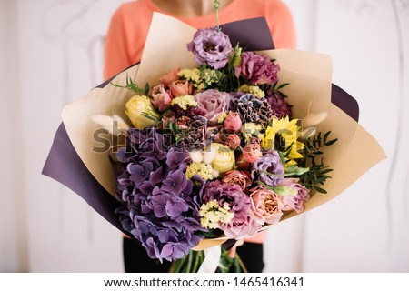 Woman's hands hold colourful blossoming flower bouquet of fresh roses living coral color on a gray b Stock photo © artjazz
