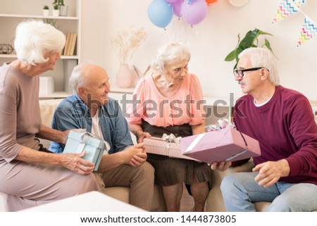 Four contemporary seniors making gifts to each other and talking Stock photo © pressmaster