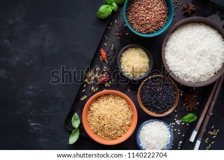 Black bowl of raw organic arborio risotto rice on white background. Healthy food.  stock photo © DenisMArt