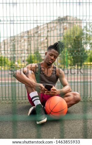 Restful African guy in sportswear scrolling or texting in smartphone Stock photo © pressmaster