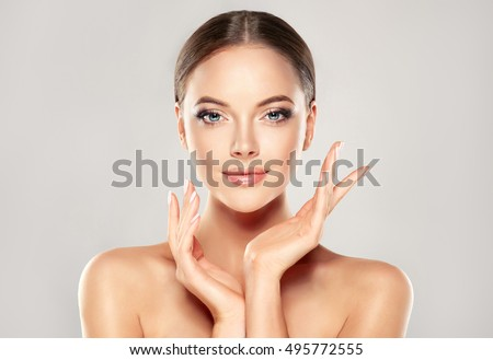 Beautiful young woman with clean fresh skin touch own face. Facial treatment Stock photo © serdechny